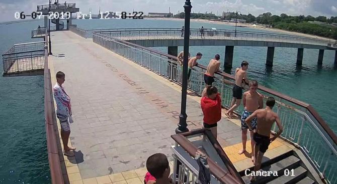Младежи в тийнейджърска възраст, практикуващи скокове в морето от Моста,