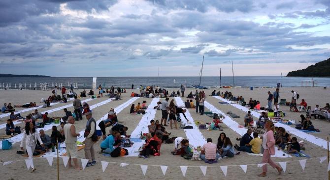 На морския бряг край Варна стотици хора вечерят заедно под